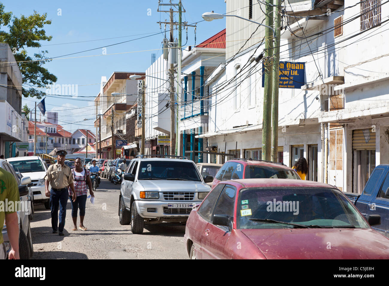Policeman walking with woman on congested street in downtown Belize City, Belize - Stock Image