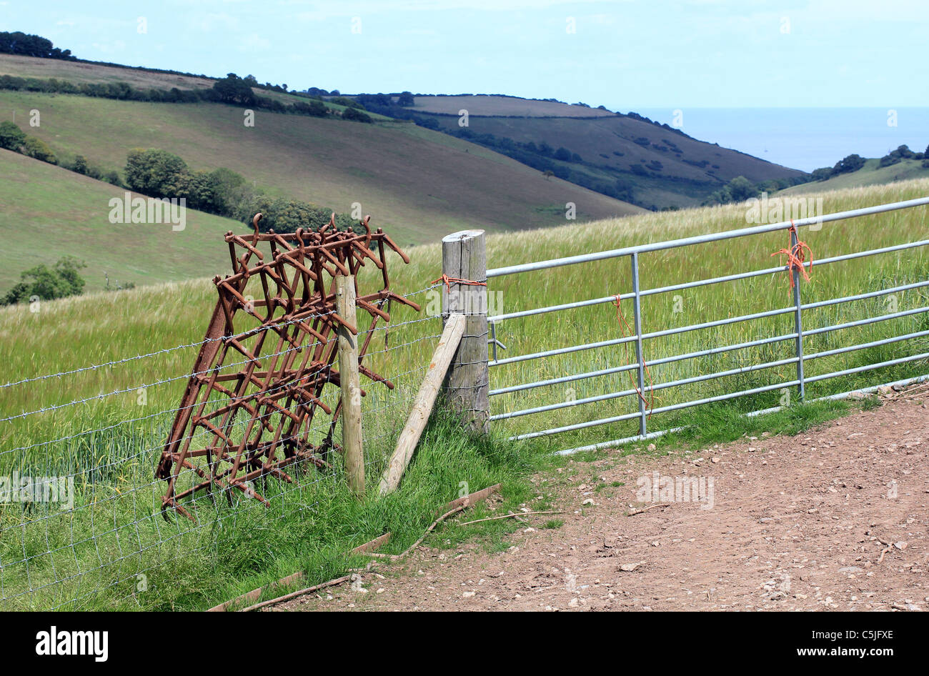 Harrow,fields Devon cove,Fence post and cloud,misc, fence, farming, keep, out, private,get of my land,farming - Stock Image