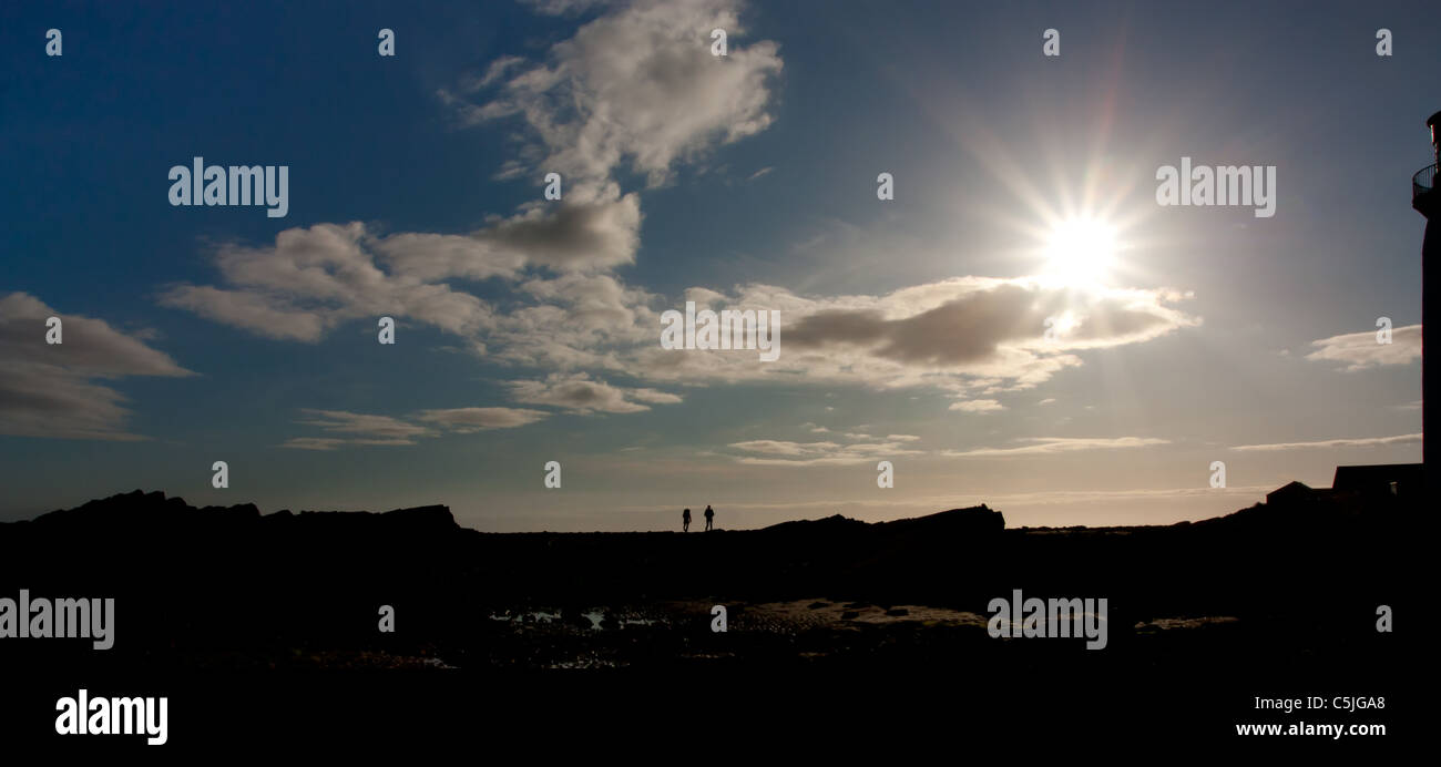 silhouetted figures by Solway Firth, Dumfries and Galloway,South West Coast, Scotland. - Stock Image