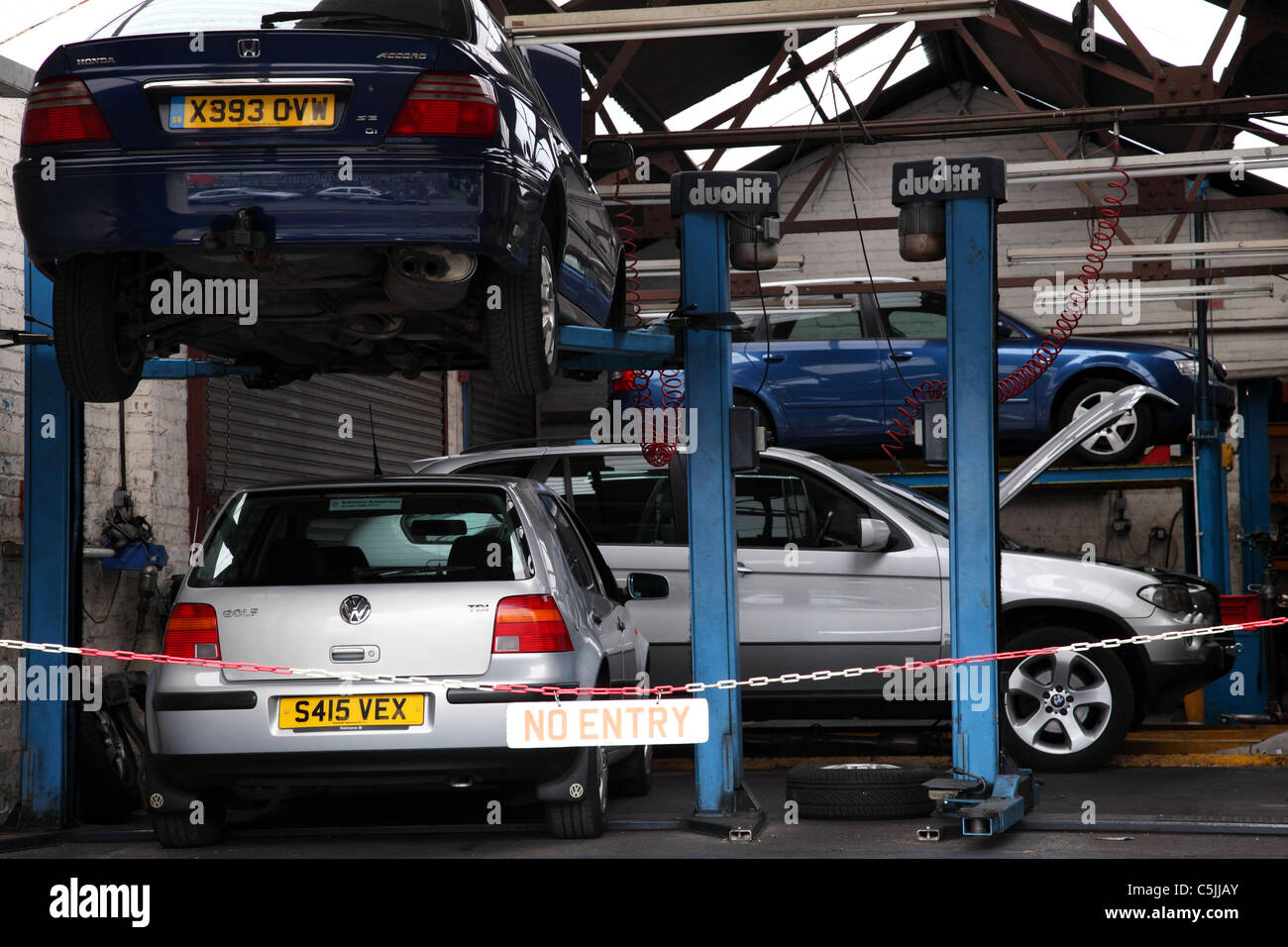 Cars being repaired in a garage in the U.K - Stock Image