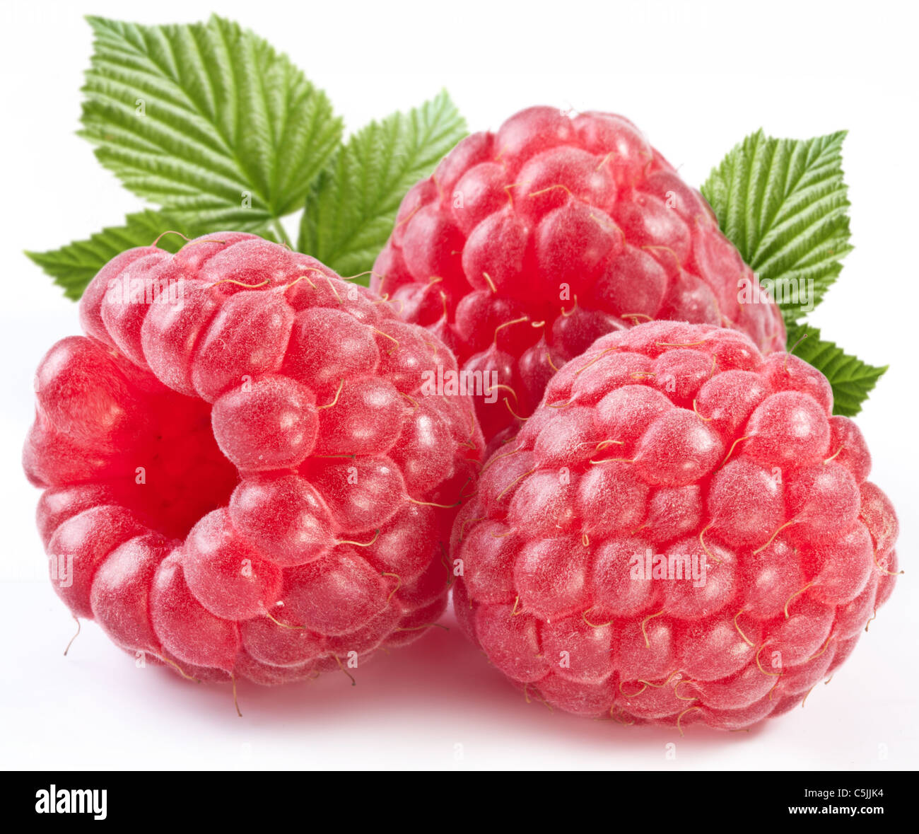 Three perfect ripe raspberries with leaves. Isolated on a white background. - Stock Image