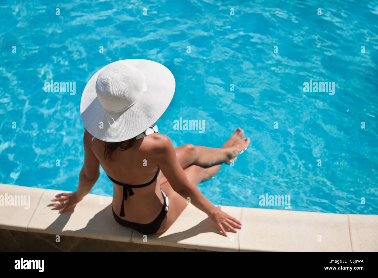 Young woman sitting on the ledge of the pool. - Stock Image