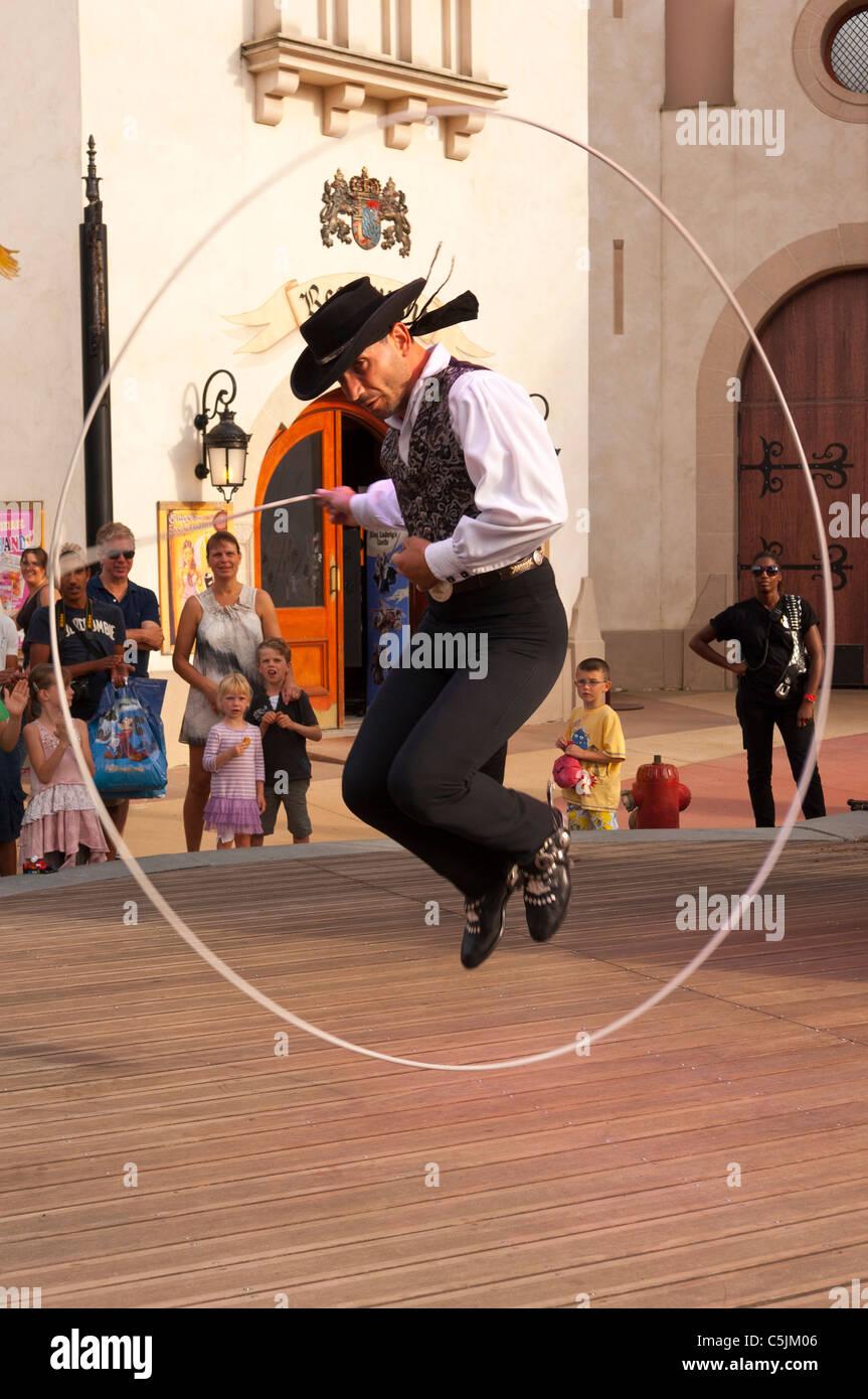 A cowboy circus performer swings his lasoo showing movement in Disney Village at Disneyland Paris in France Stock Photo