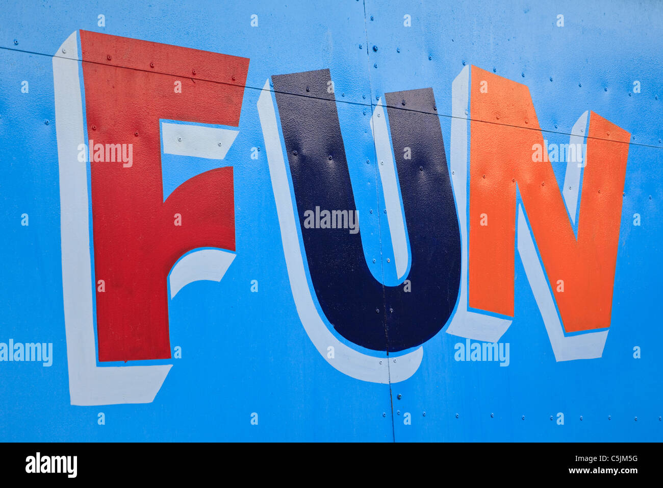 The word Fun painted in bright colours on a blue door - Stock Image