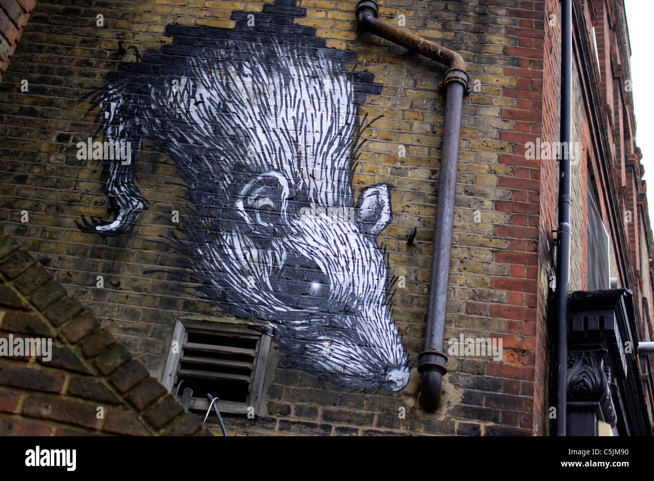Giant rat painted onto the side of a building near Aldgate, London - Stock Image
