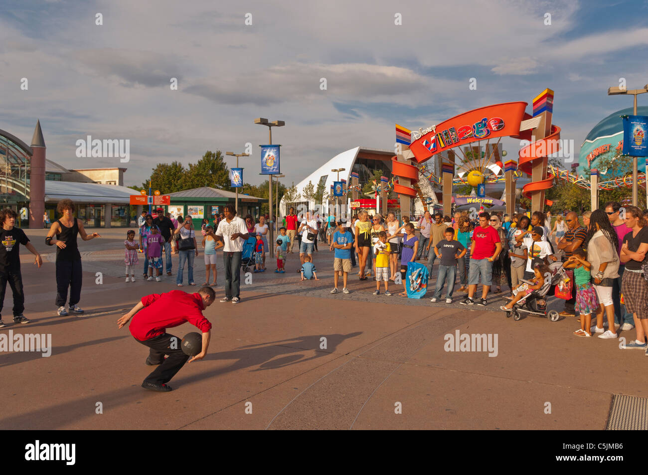 A street performer busking outside the entrance to Disney Village at Disneyland Paris in France - Stock Image