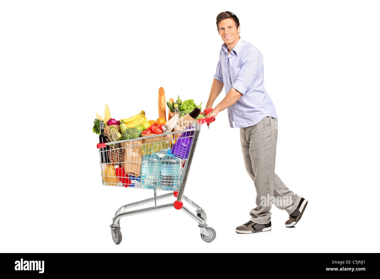 A young male pushing a shopping cart full with groceries - Stock Image
