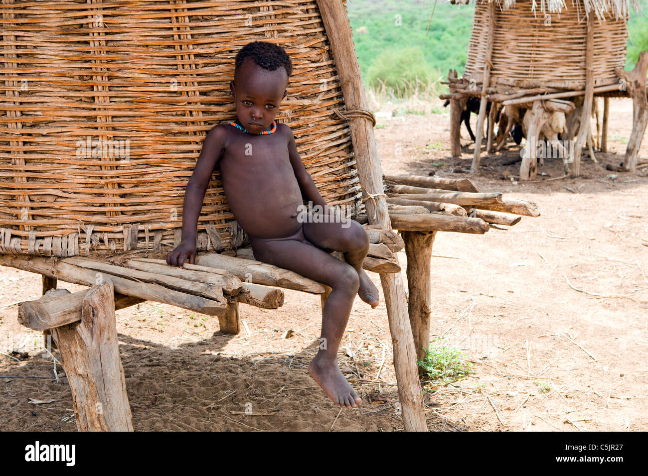 A child finds shade beside a stilted grainstore at the Karo village of Kolcho in the Lower Omo Valley, Southern - Stock Image