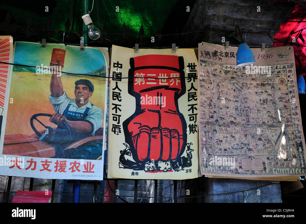 Cultural Revolution era (1960's to 70's) propaganda posters are for sale in a stand. Beijing, China. - Stock Image