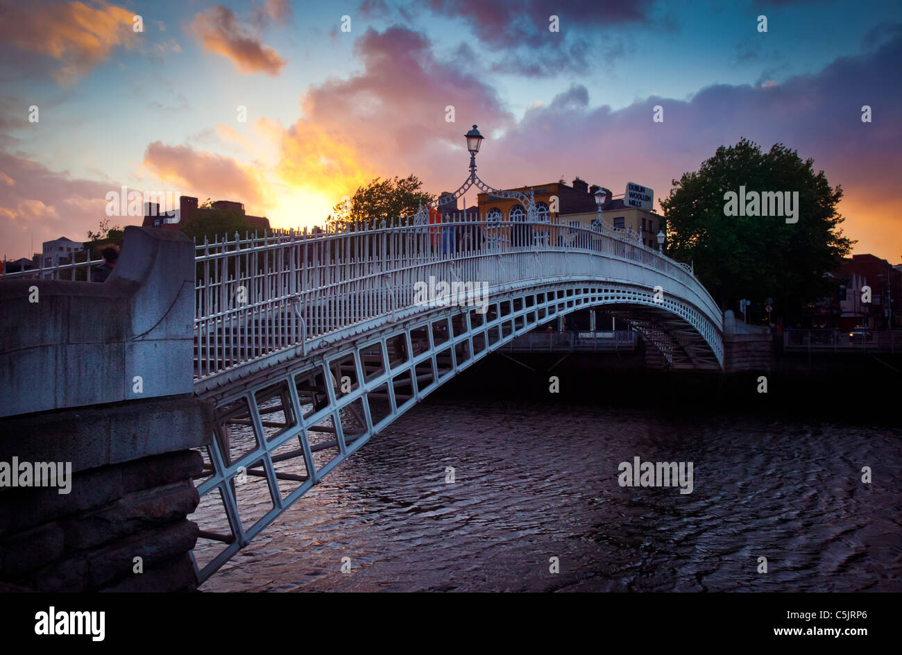 Liffey, or Ha'Penny, Bridge in Dublin, Ireland at dusk - Stock Image