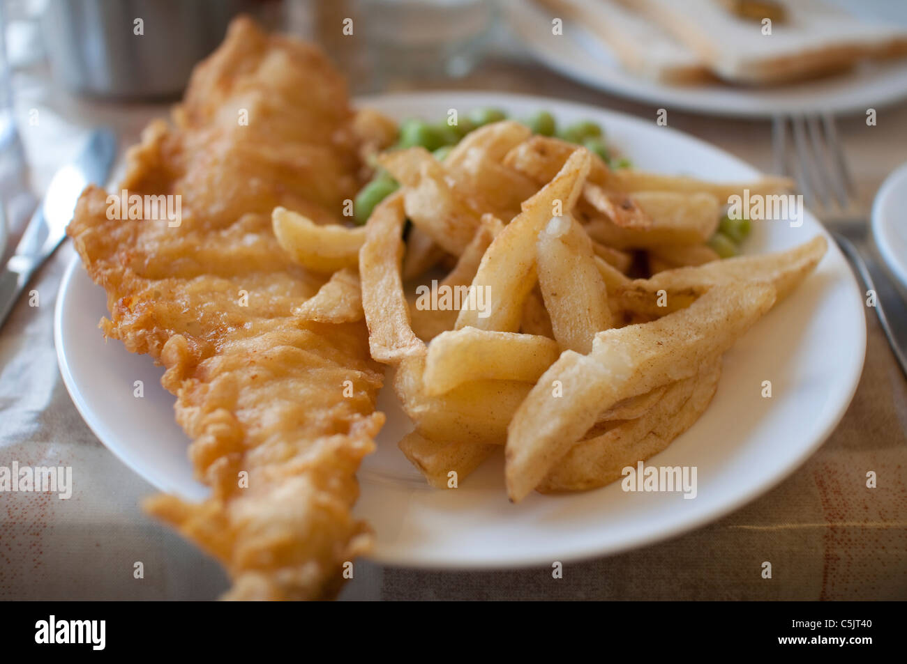 Fish and Chips served with mushy peas on a plate in England. - Stock Image