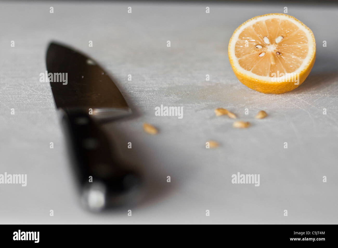 A knife and lemon half on a white cutting board. - Stock Image