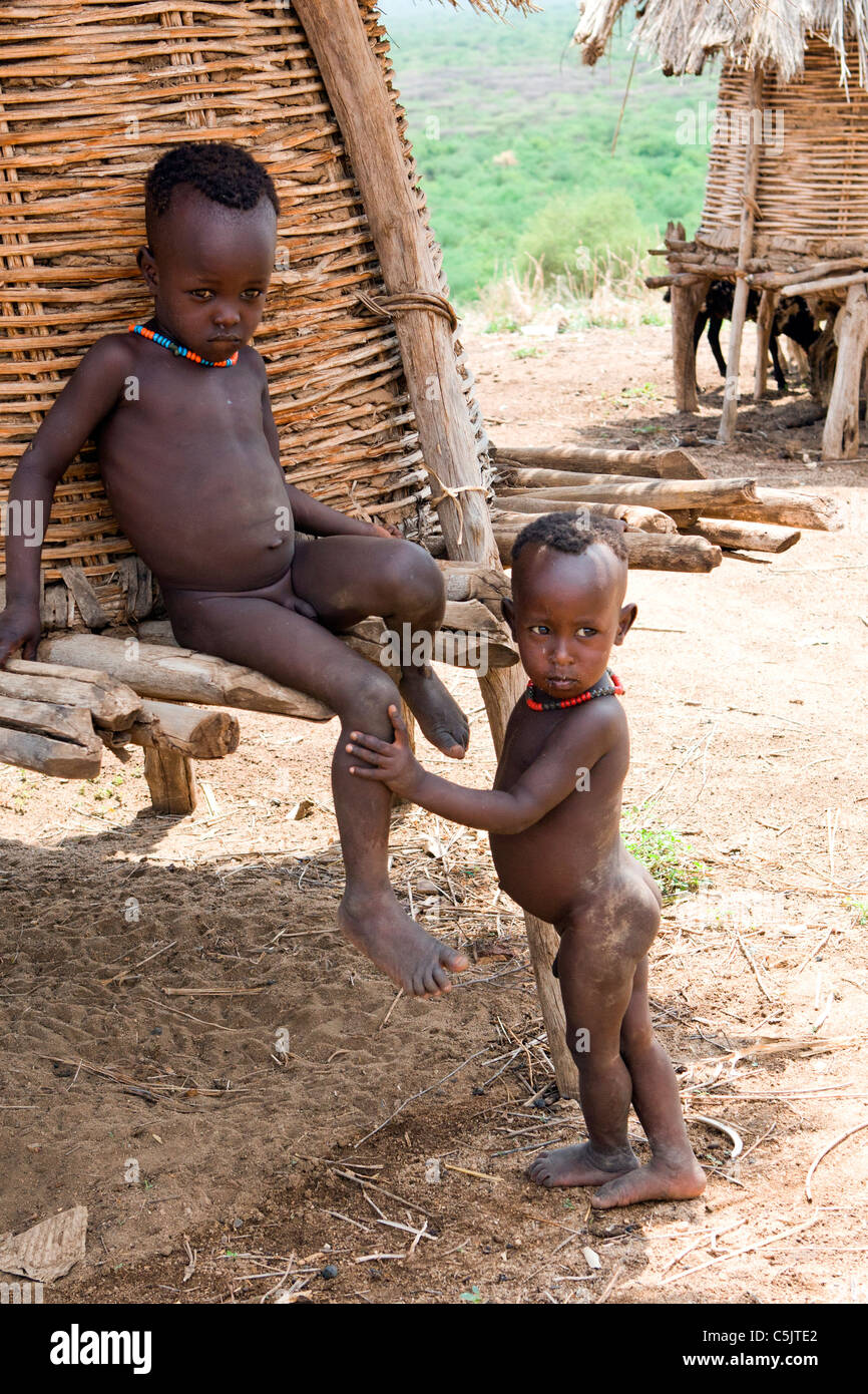 Children of the Karo tribe find shade beside a stilted grainstore at the village of Kolcho in the Lower Omo Valley, - Stock Image