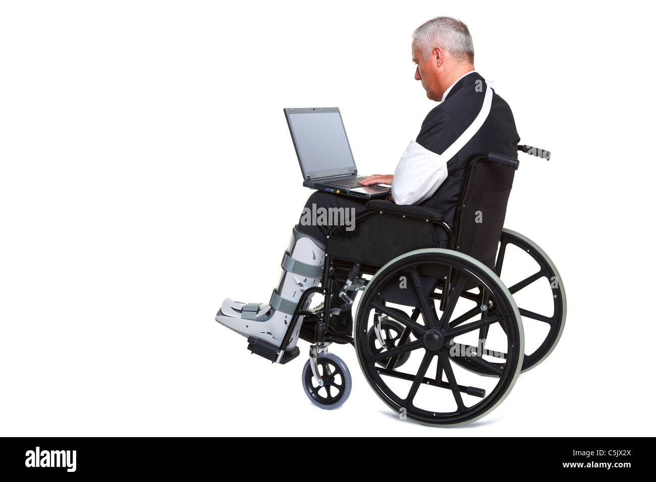Photo of an injured businessman sitting in a wheelchair working on a laptop computer, isolated against a white background. - Stock Image