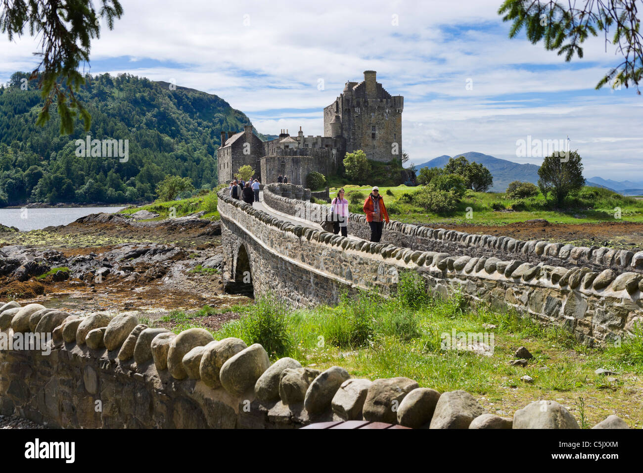 Tourists crossing the bridge to Eilean Donan Castle, Loch Duich, Highland, Scotland, UK - Stock Image