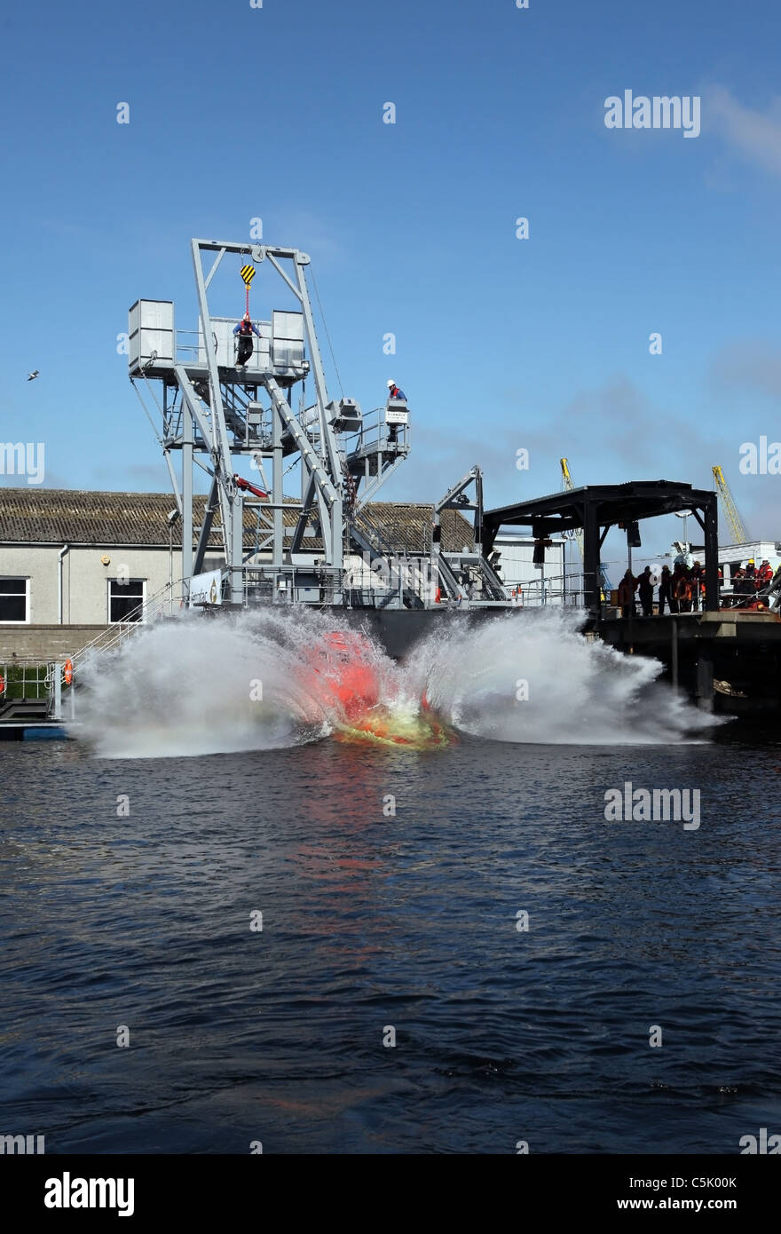 Sequence (see other images) of a free fall lifeboat trainer being dropped into the water. - Stock Image