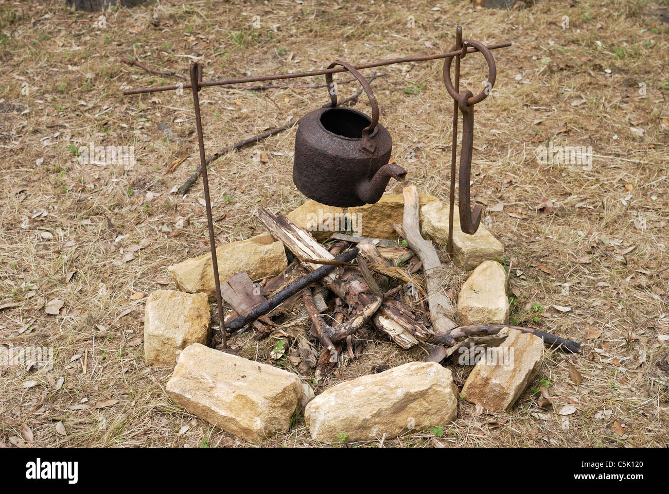 Old rusty kettle on iron frame over an unlit open fire outside in countryside - Stock Image