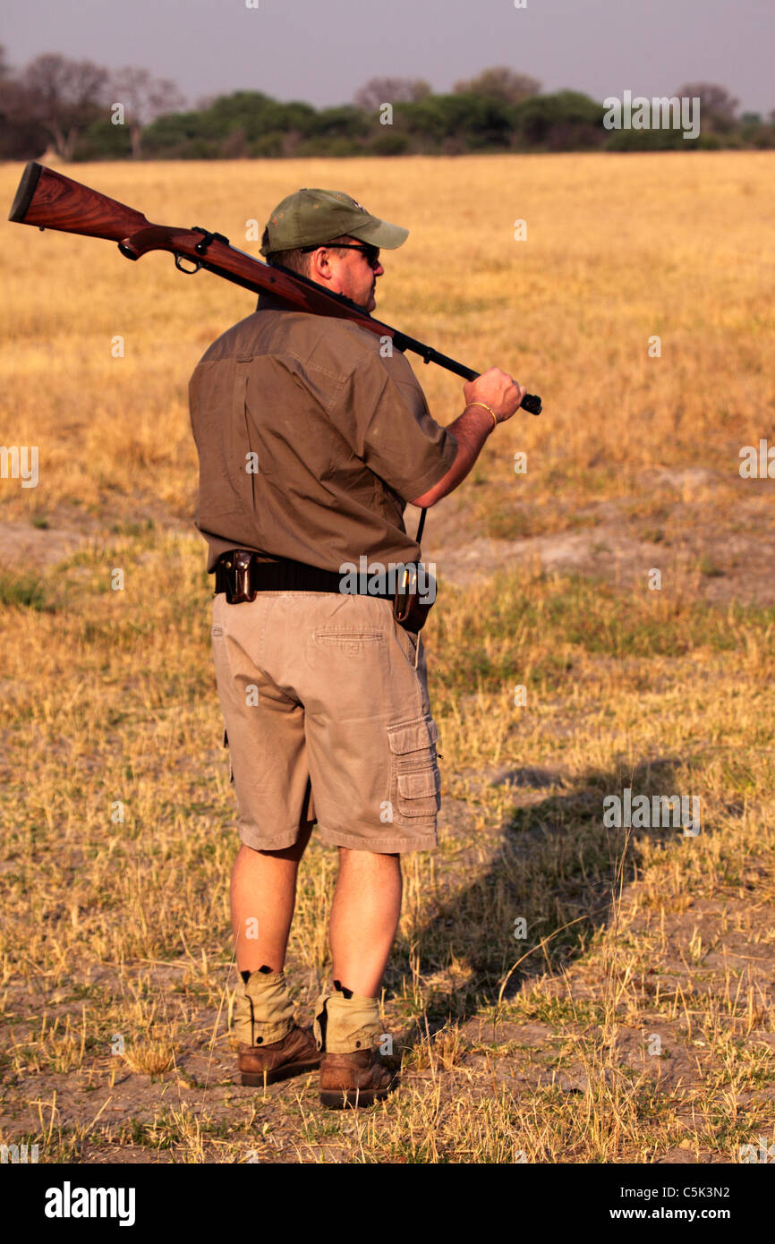 A nature guide carries a rifle on a morning walk in Hwange National Park, Zimbabwe. Stock Photo