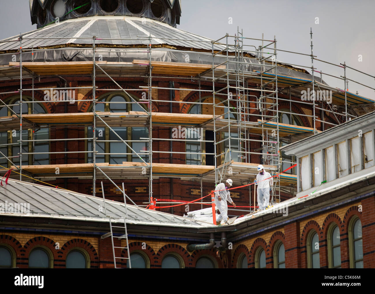Building restorers working roof of historic Smithsonian's Arts and Industries Museum - Stock Image