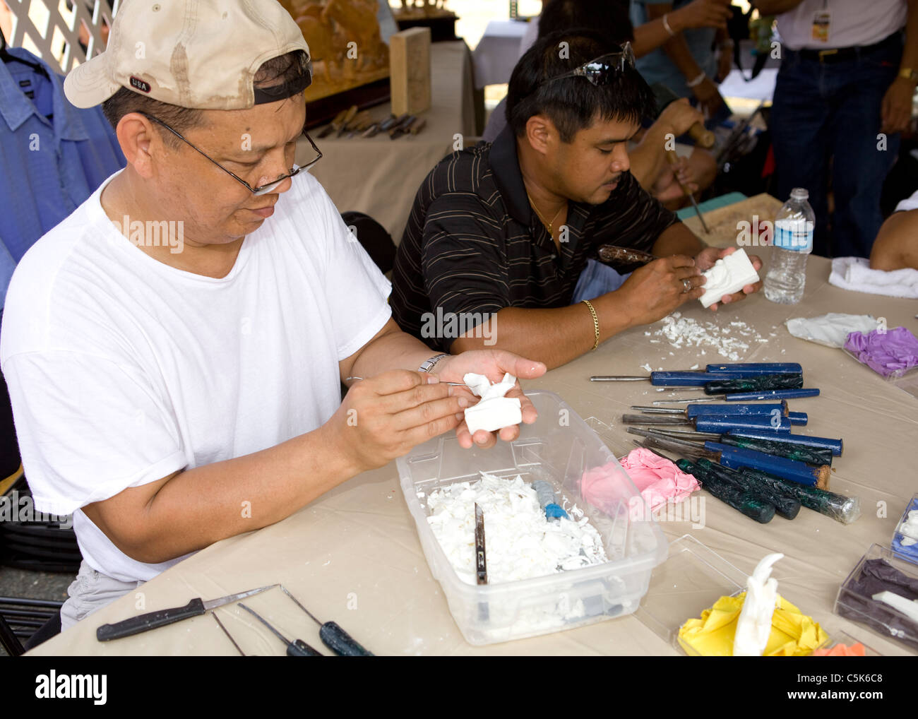 An Asian man carving a small figure from soap bar - Stock Image