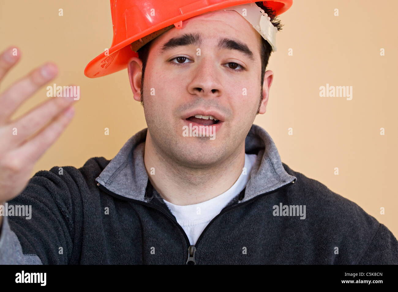 This young construction worker has his hard hat on sideways. - Stock Image