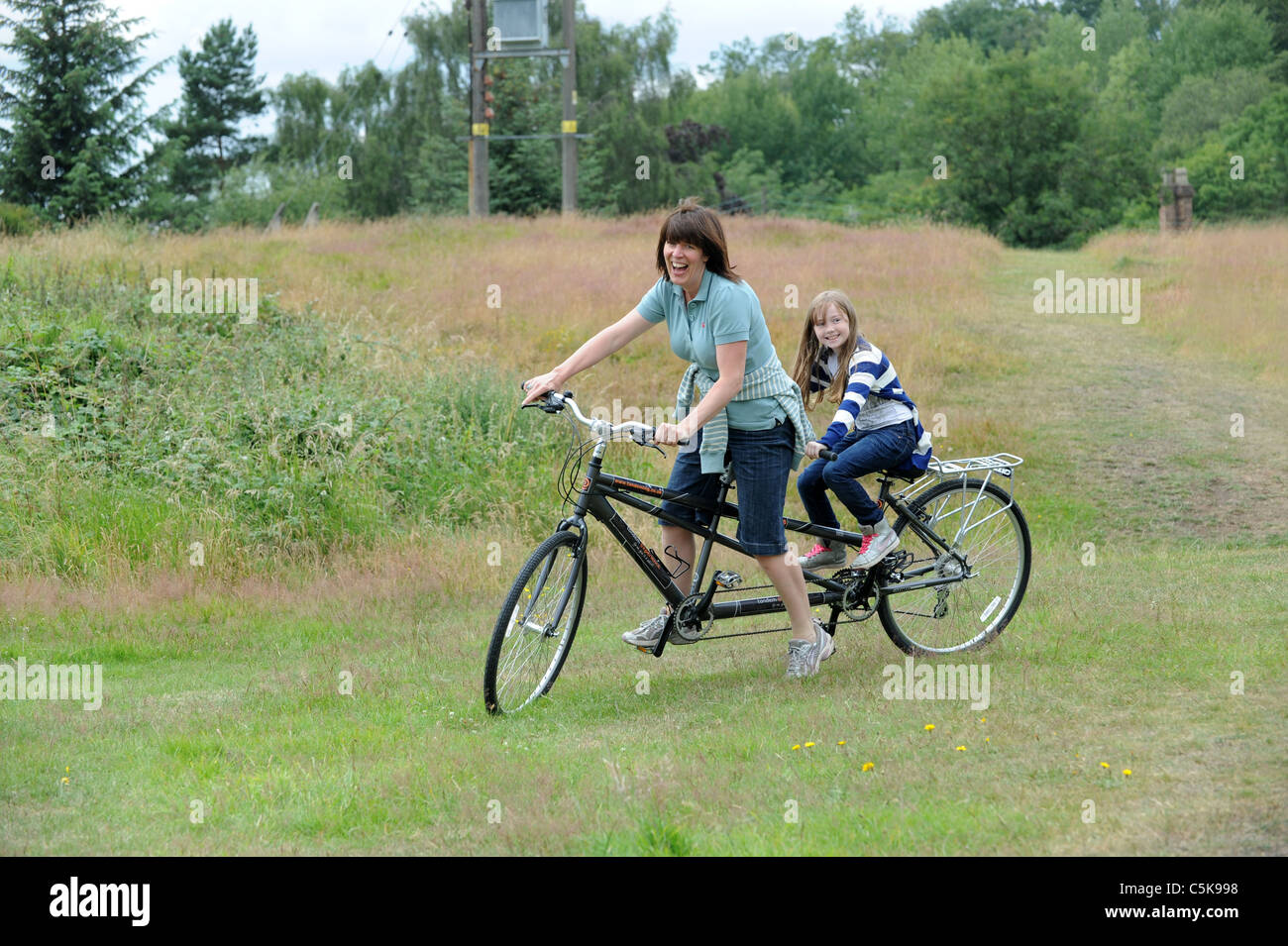 Woman and child having fun on tandem bicycle - Stock Image