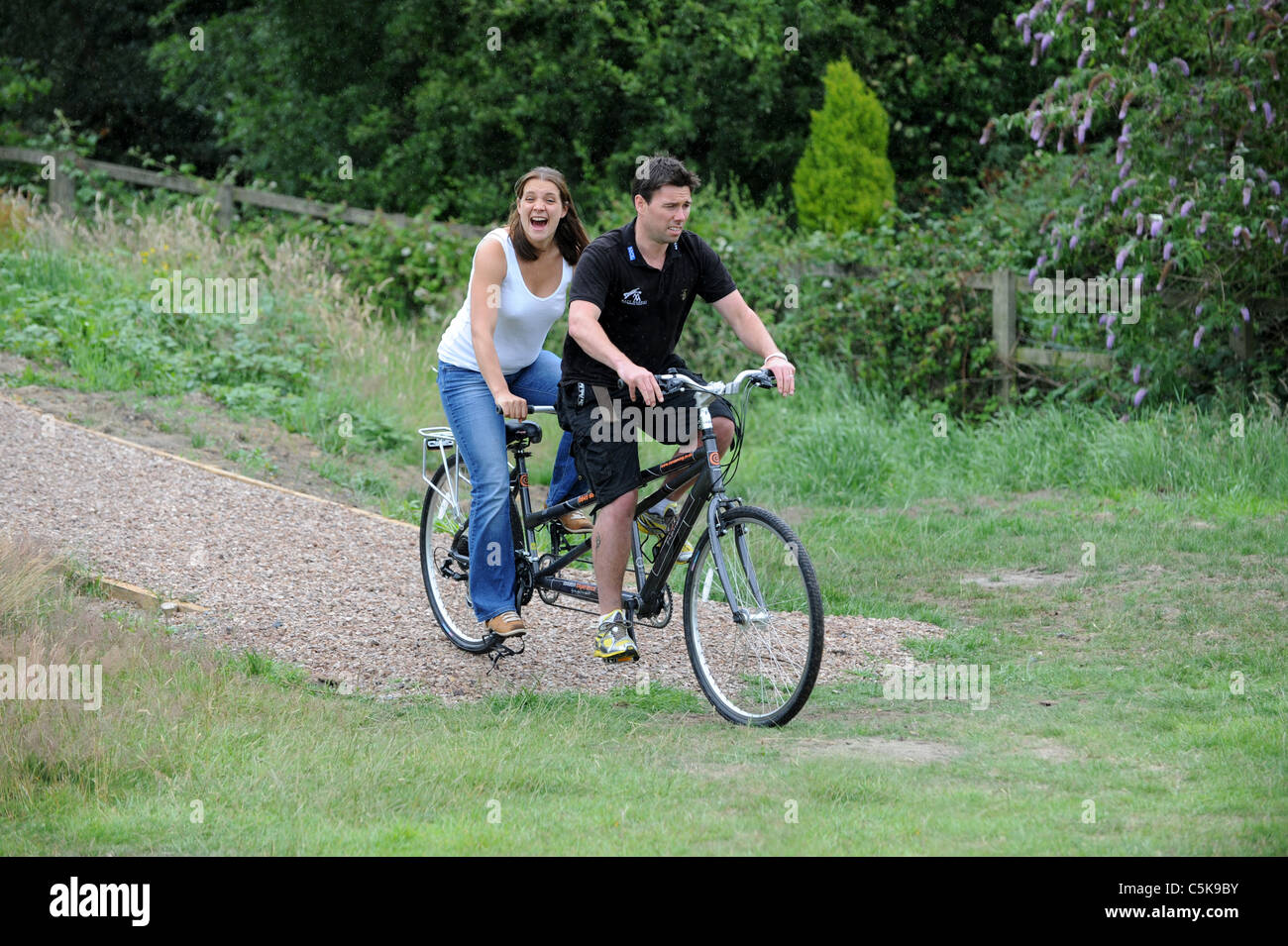 Woman and man having fun on tandem bicycle uk - Stock Image