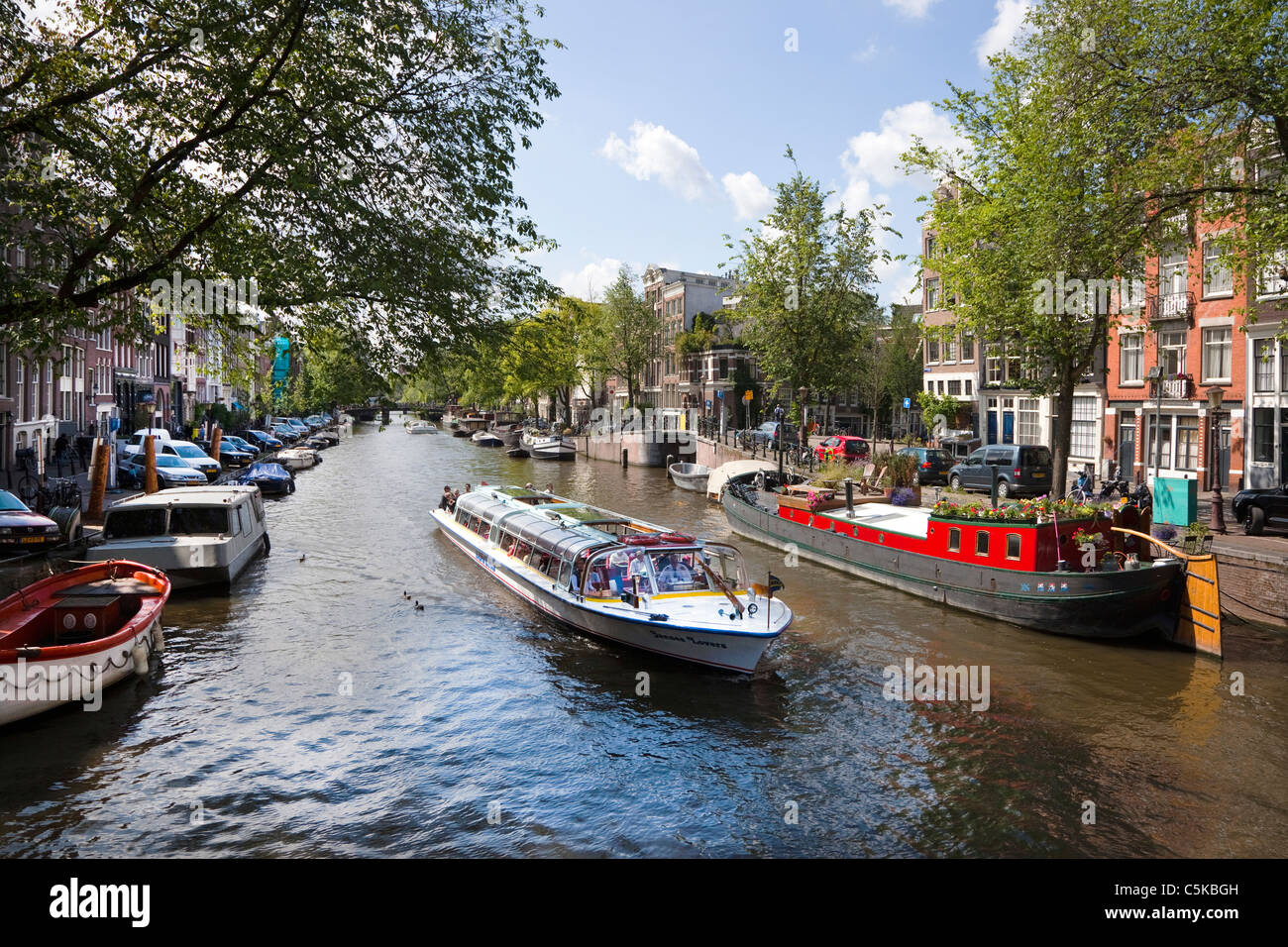Tourist canal boat sailing along a canal in Amsterdam, Netherlands - Stock Image