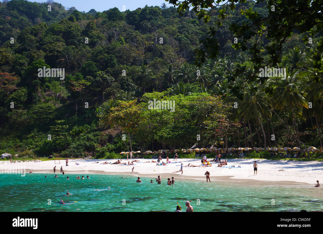 View over iconic tropical beach at 'Paradise Beach' with people on the beach and in the sea - Stock Image