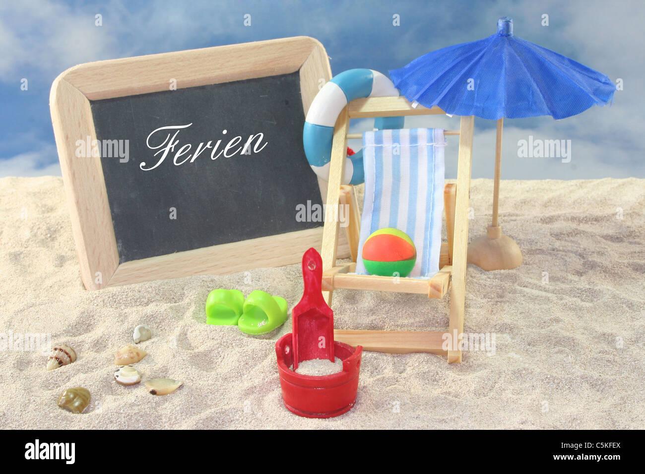 School board and toys on a sandy beach Stock Photo