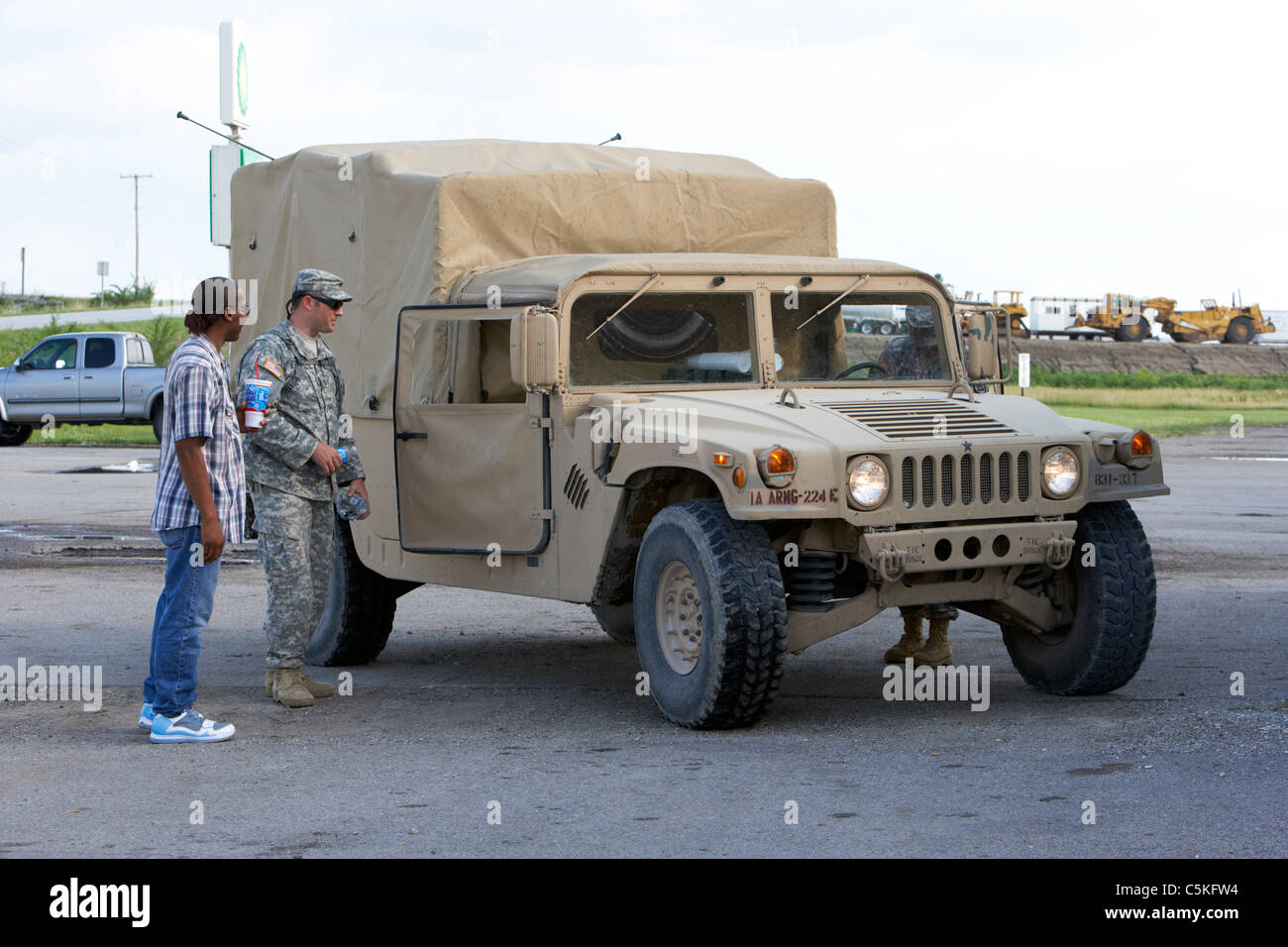 local man talks to Iowa army national guard soldiers at humvee united states military in front of levees at the - Stock Image