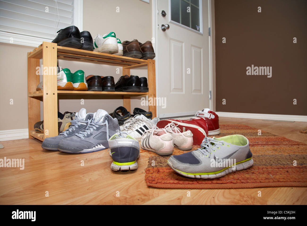 pile of shoes inside the front door of a house in Canada to keep carpets and floors clean - Stock Image