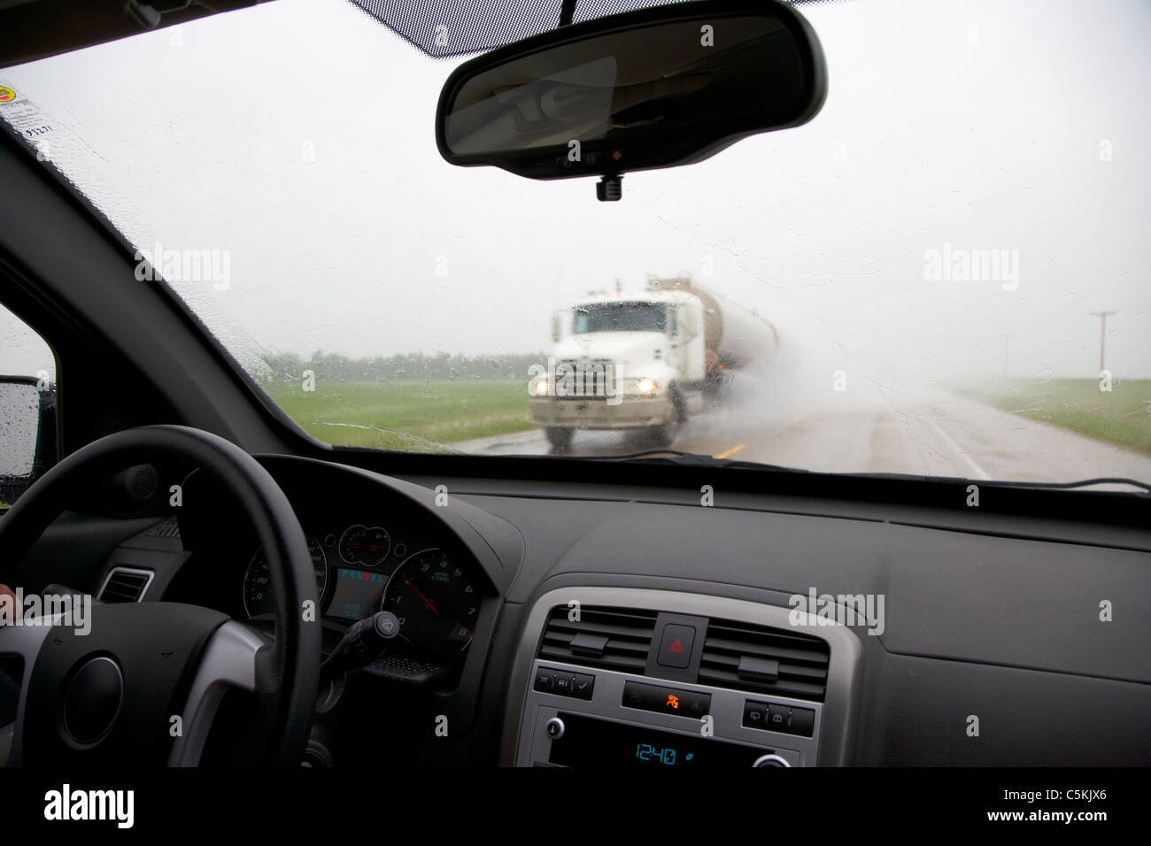 car driving through heavy rainstorm and flooding with oncoming truck in southern saskatchewan canada - Stock Image