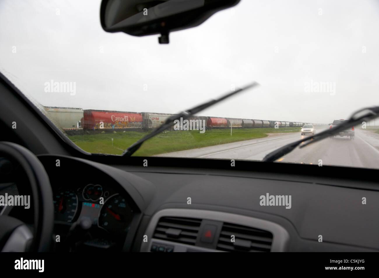 car driving through heavy rainstorm passing train in southern saskatchewan canada - Stock Image