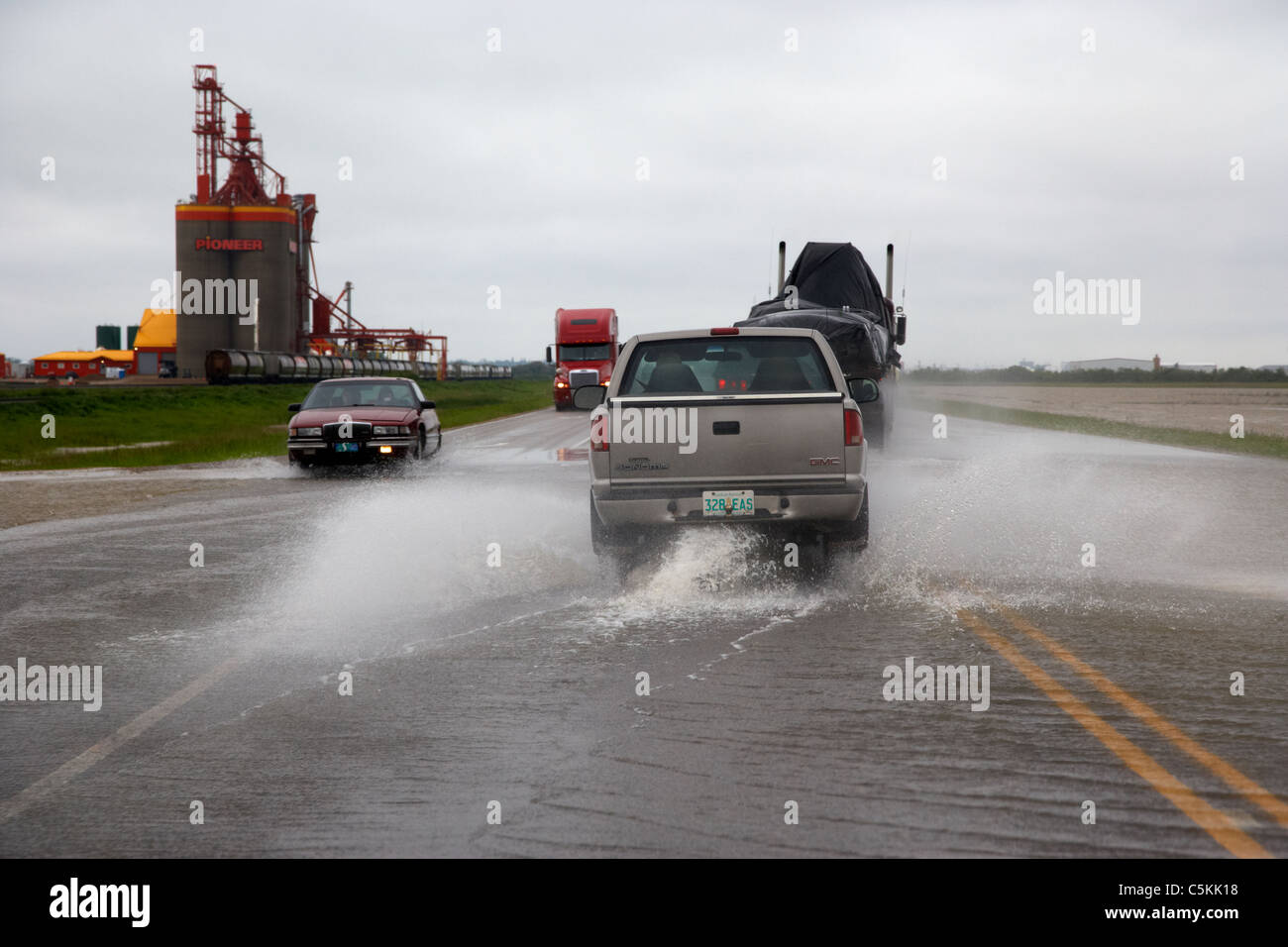 cars driving through heavy rainstorm and flooding roads in southern saskatchewan canada - Stock Image