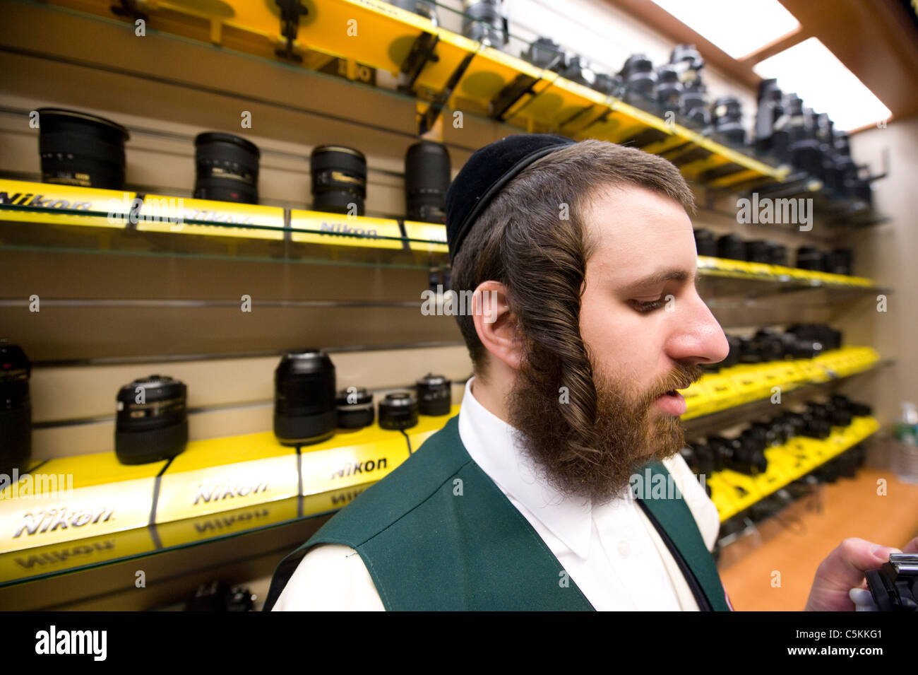 Jewish man in front of a Nikon lens display in a camera store, New York City. © Craig M. Eisenberg - Stock Image