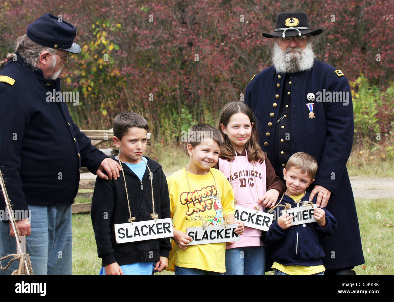 Two Union soldiers holding young children under arrest wearing signs of their sins such as slacker and thief - Stock Image
