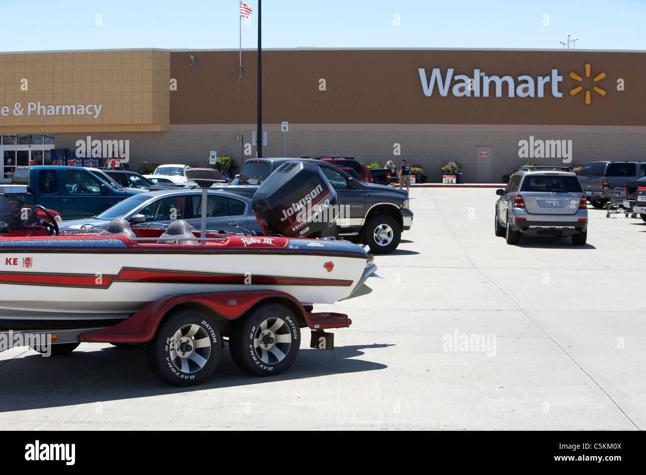 boat and cars parked in the parking lot of a large walmart store in