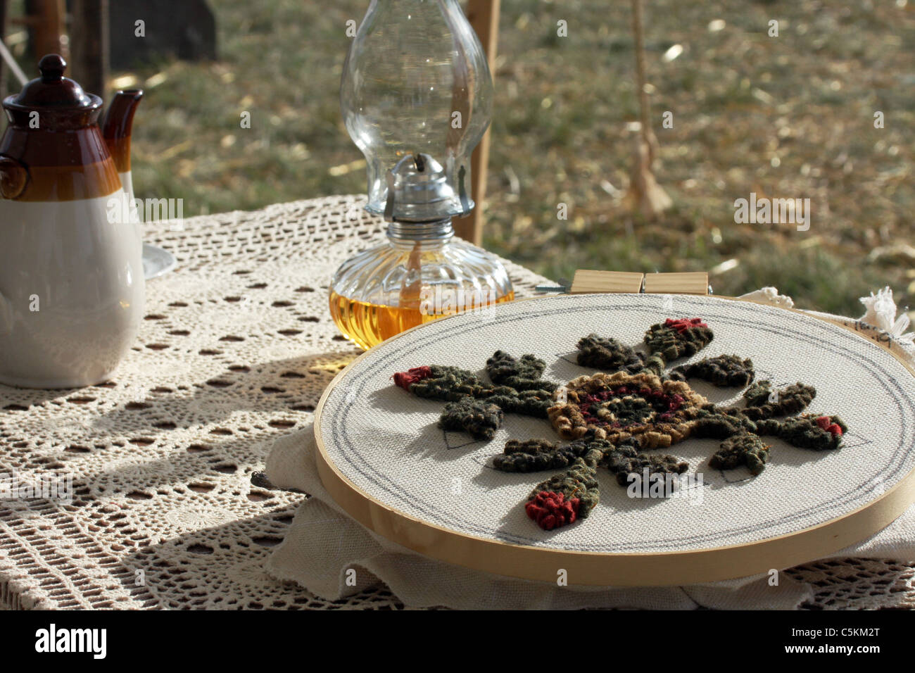 Handmade rugging decoration on a civil war time period next to an oil lamp and water pitcher - Stock Image