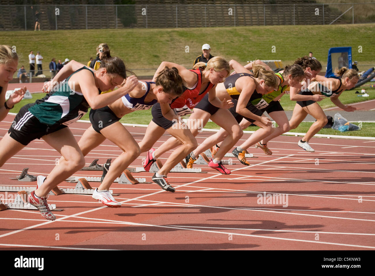 A row of girls at the start of a sprint race on a running track, Wellington, New Zealand - Stock Image