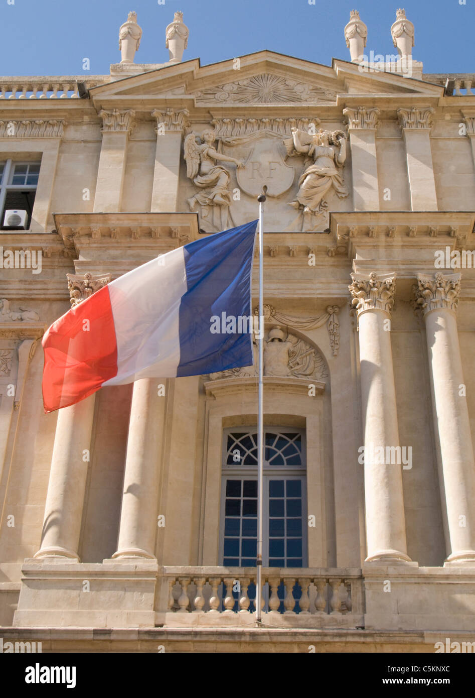 Detail of façade of the Marie (Town Hall) of Arles, France, with French flag and national crest with - Stock Image