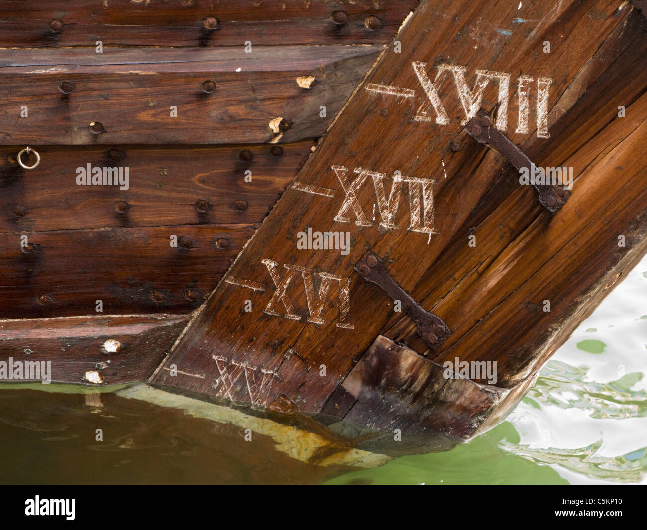 Draft marks in Roman numerals on rudder of an old wooden barge at a wharf on The Creek, Dubai, United Arab Emirates - Stock Image