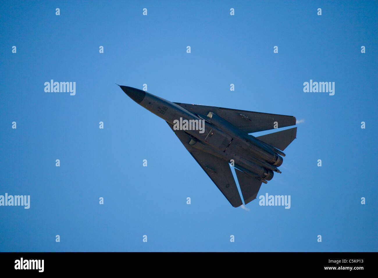 General Dynamics F-111 jet fighter aircraft of Royal Australian Air Force from below, flying at speed with wings - Stock Image