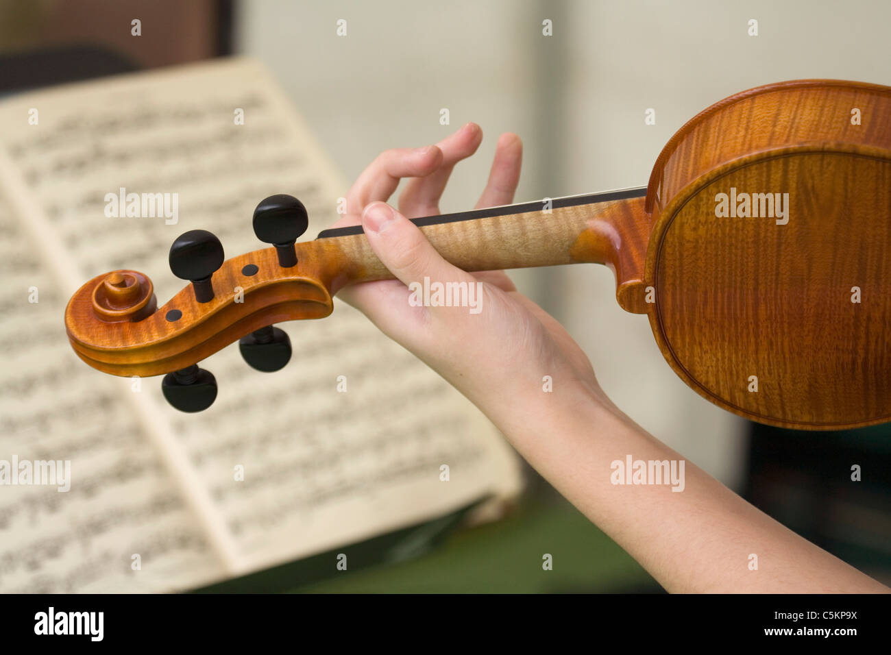 Left hand and arm of young woman playing a violin, printed musical score in background - Stock Image
