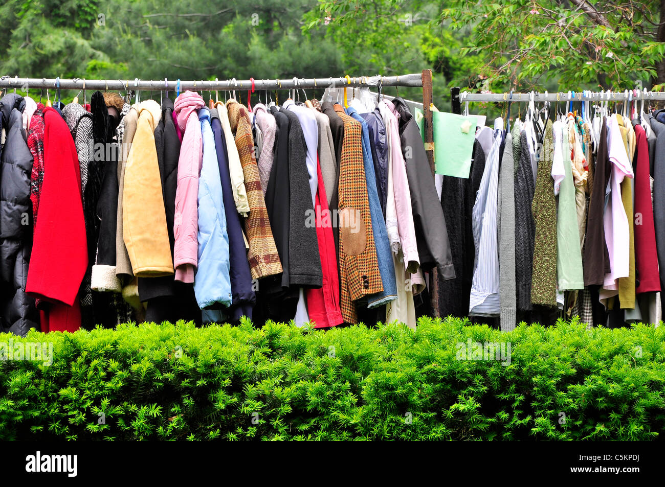 Large number of clothes hanging outside for sale in New York City. - Stock Image