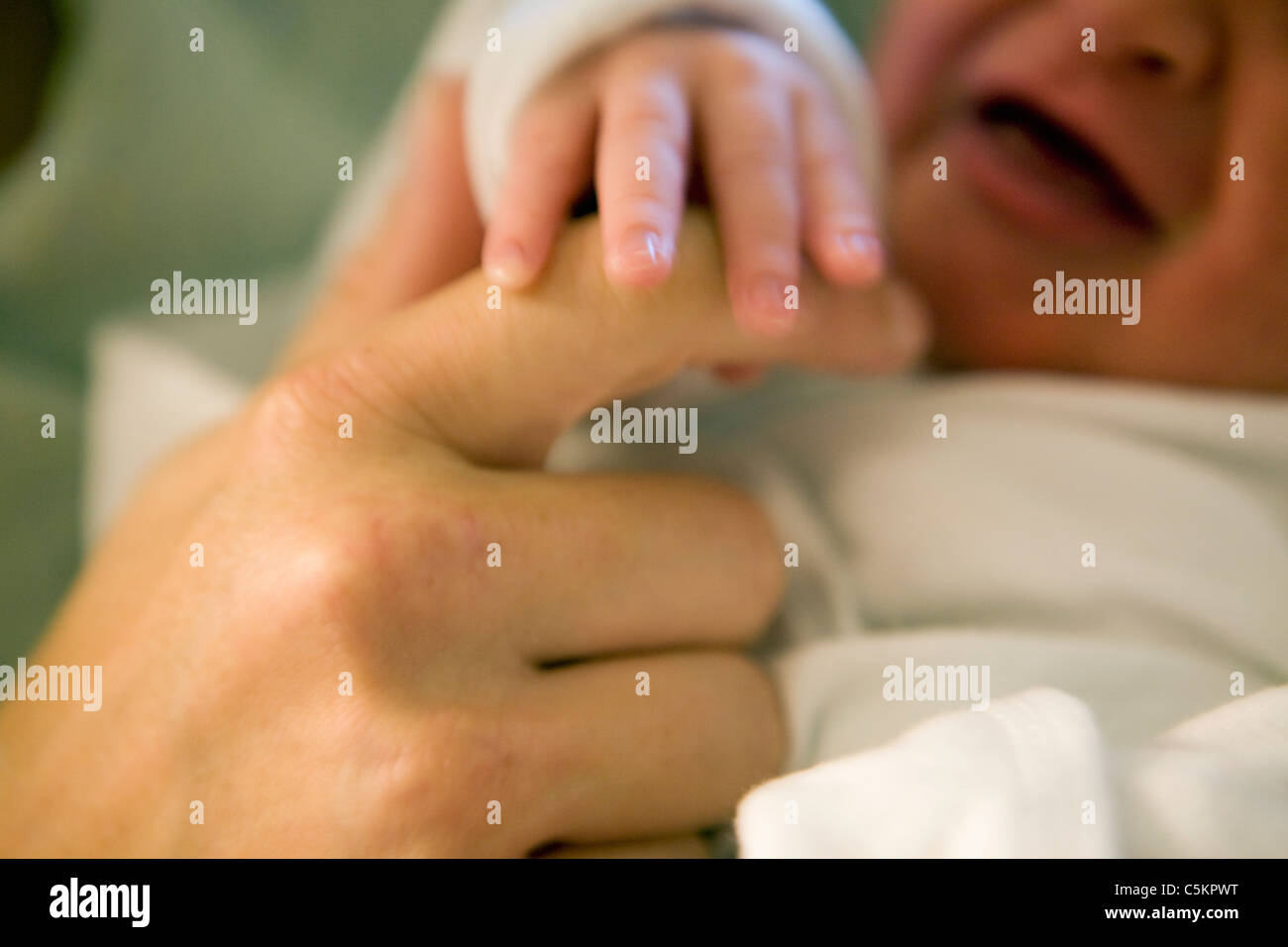 Newborn's hand on mothers hand.  Newborn baby hand.  Crying baby holding mothers hand. - Stock Image