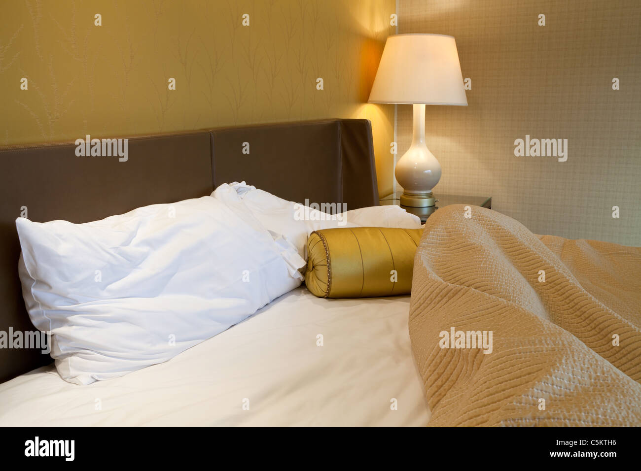 Messy king sized bed with pillow and quilt cover - Stock Image