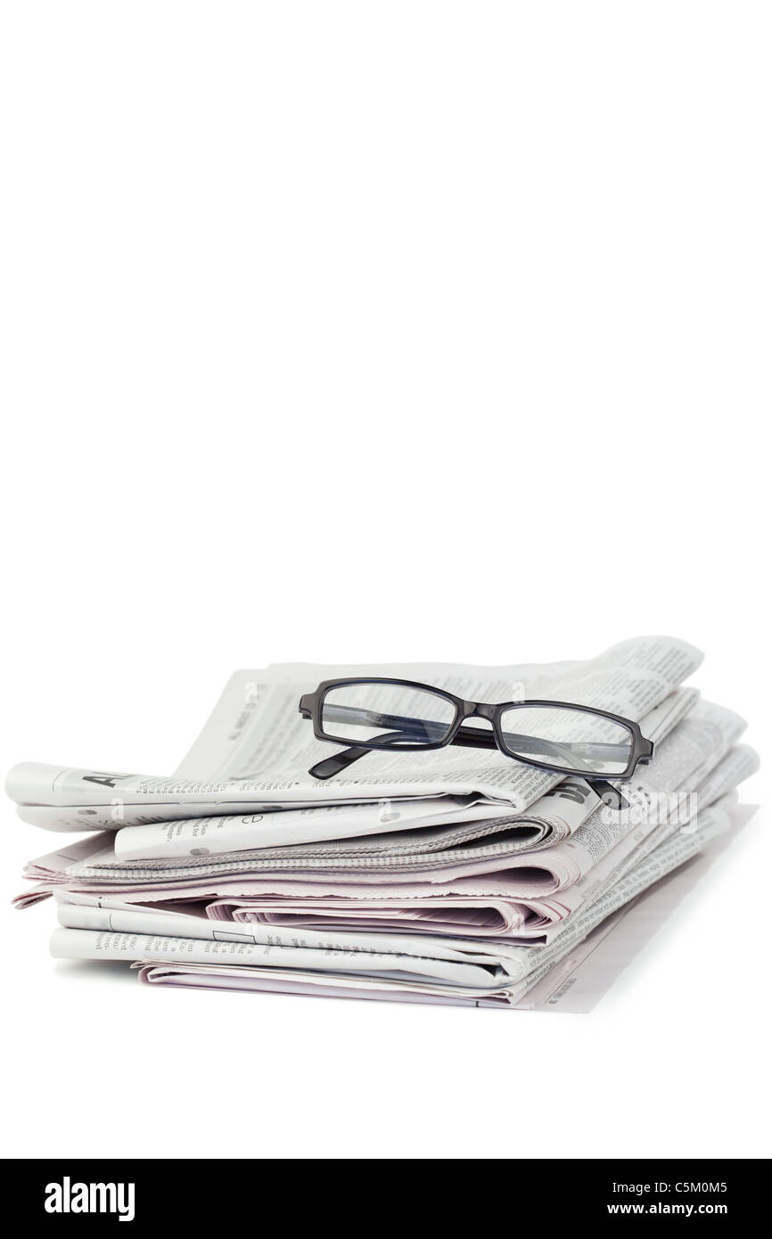 A pair of reading glasses on top of a pile of newspapers Stock Photo
