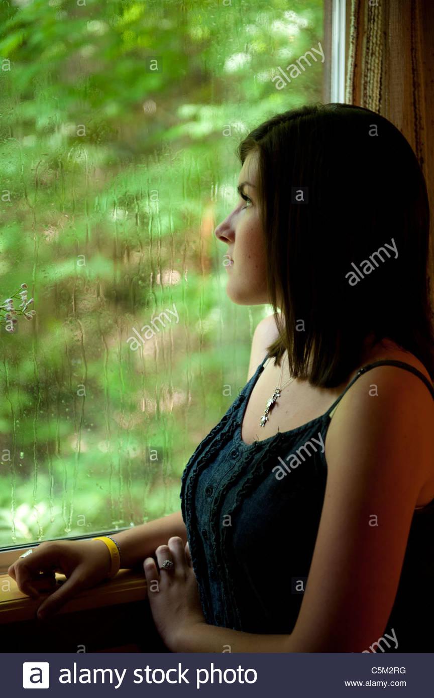 Melancholy Girl at rainy window - Stock Image