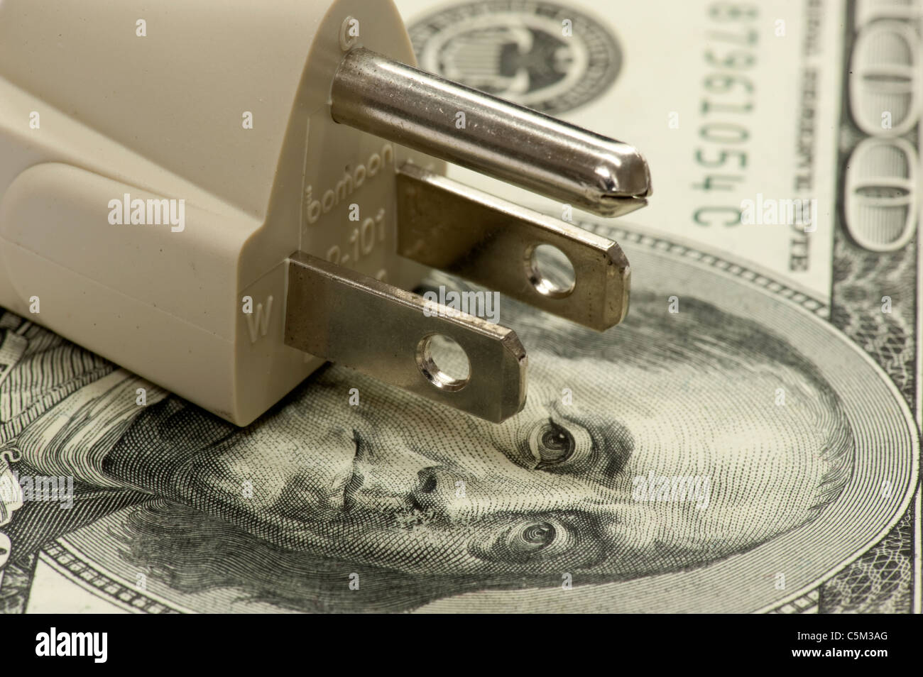 electrical plug on US one hundred dollar bill - Stock Image